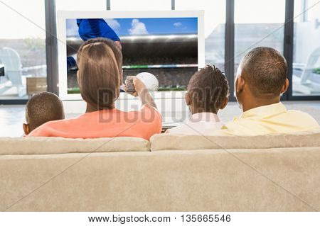 Football player kicking ball against over shoulder view of casual family watching tv