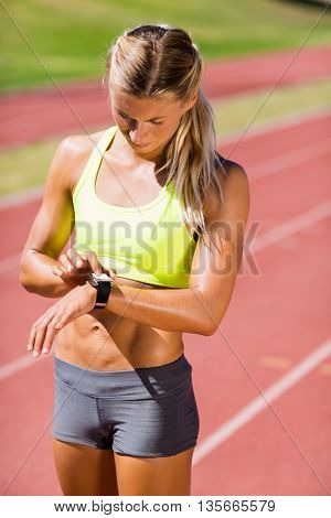 Female athlete checking her smart watch on running track
