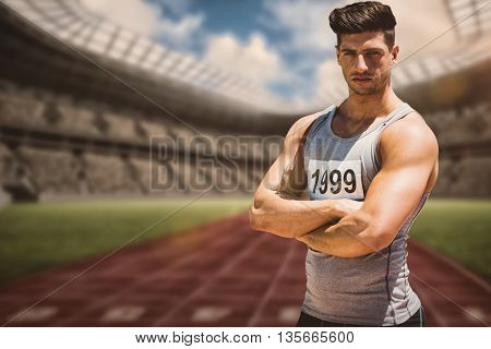 Portrait of handsome sportsman is posing with crossed arms against view of a running track