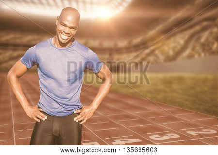 Sportsman smiling and posing on a white background against athletic track in a stadium