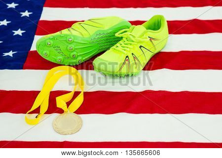 Green trainer shoes and gold medal on american flag