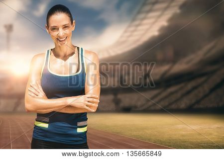 Sportswoman posing and smiling on a white background against view of a stadium
