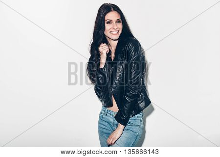 Cheerful beauty. Beautiful young woman in unbuttoned leather jacket posing against grey background and smiling