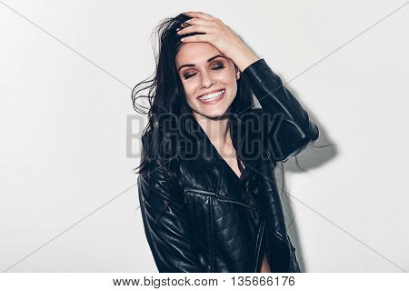 Feeling carefree. Beautiful young smiling woman in unbuttoned leather jacket holding hand in hair and keeping eyes closed while standing against grey background