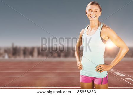 Fit woman posing and smiling against athletic track on a cityscape