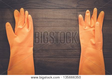 orange rubber cleaning gloves on wooden background