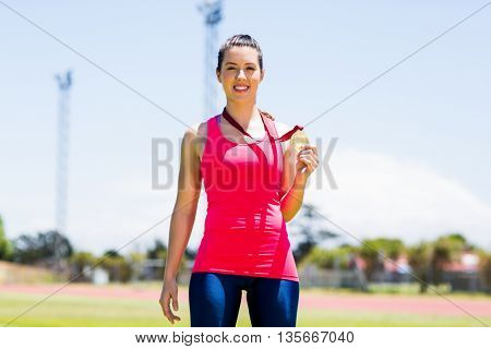 Portrait of happy female athlete showing her gold medal