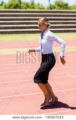 Businesswoman running on a running track on a sunny day
