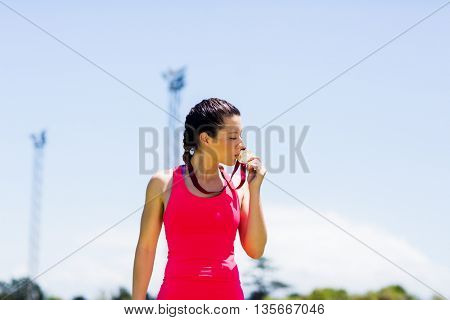Female athlete kissing her gold medals in stadium