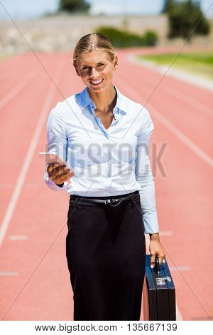 Portrait of businesswoman standing with mobile phone and briefcase on a running track