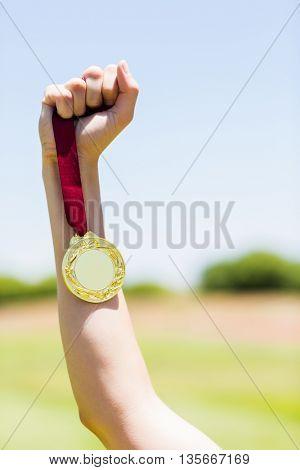 Hand of female athlete holding gold medal in stadium