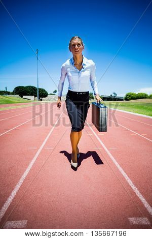 Businesswoman with briefcase running on a running track