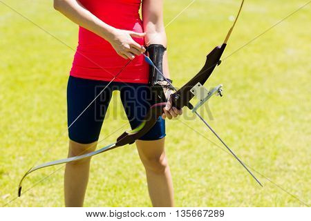 Mid-section of female athlete practicing archery in stadium