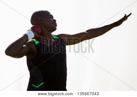 Male athlete preparing to throw shot put ball on white background