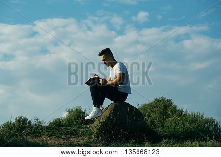 Pensive Muscular Man With Book Outdoor