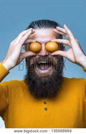 handsome bearded man with long lush beard and moustache on smiling face holding egg in yellow shirt in studio on blue background