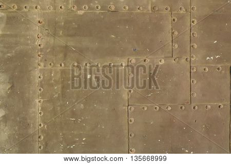 Old rusty grunge steel fragment of metal sheets assembled with rivets on armor textured background
