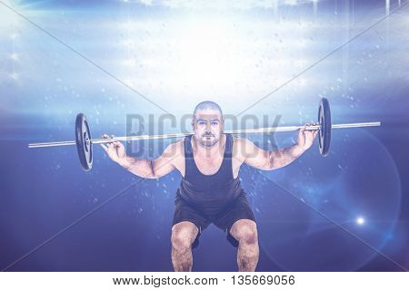 Bodybuilder lifting heavy barbell weights against digitally generated image of spotlight against black background