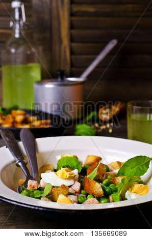 Salad with green peas bacon and croutons on wooden background. Selective focus.