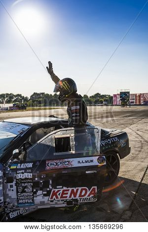 VinnytsiaUkraine-July 25 2015: Racer Dmytro Illyuk welcomes visitors near the track in the Drift championship of Ukraine on July 252015 in Vinnytsia Ukraine.