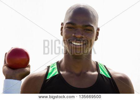 Portrait of male athlete holding shot put ball in stadium