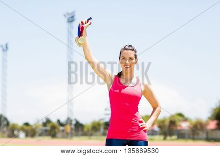 Portrait of happy female athlete showing her gold medals