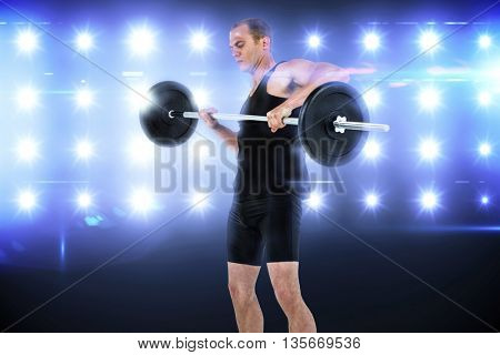 Bodybuilder lifting heavy barbell weights against composite image of blue spotlight