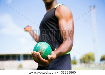 Mid section of athlete holding hammer throw in stadium