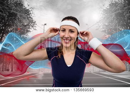 Female athlete wearing headband and wristband against composite image of tennis field on a sunny day