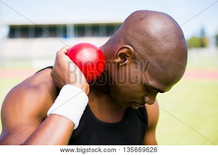 Male athlete holding shot put ball in stadium