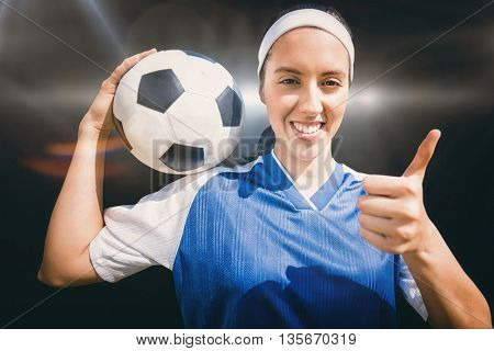 Portrait of happy woman football player holding a football against spotlight
