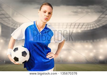 Portrait of woman football player is posing against sports arena