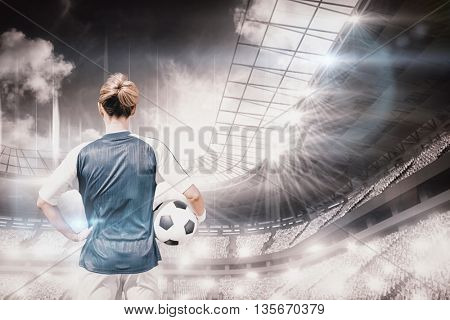 Rear view of woman football player posing against sports arena