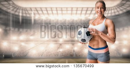 Female athlete holding a soccer ball against sports arena