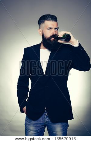 Handsome young man with long beard and moustache in black jacket holding green glass beer bottle in studio on grey background