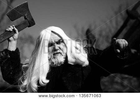 Brutal druid old man with long silver hair and beard in fur coat with axe in hand black and white on grey sky background