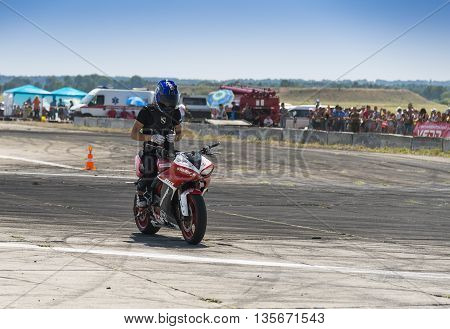VinnytsiaUkraine-July 25 2015: Unknown stunt biker entertain the audience before the start of the championship of drifting on July 25 2015 in Vinnytsia Ukraine.