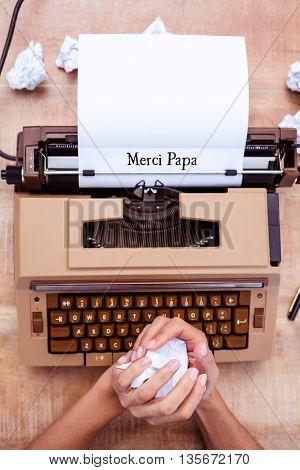 Hands crumpling paper in front of typewriter