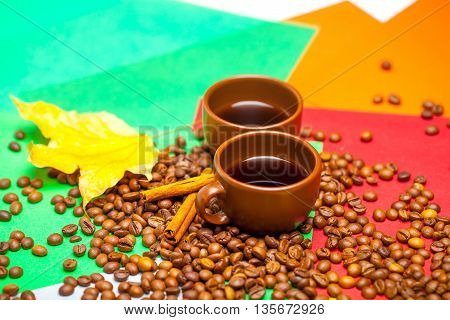 two coffe cups brown color with many beans near yellow autumn maple leaf and cinnamon sticks on bright colorful white background