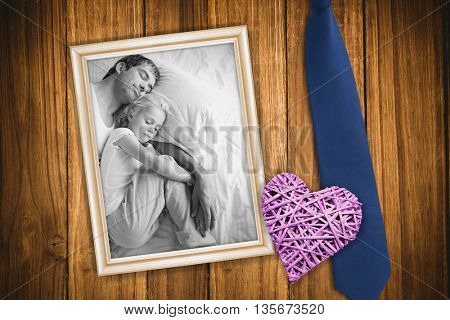 Father and daughter sleeping on bed against wooden background