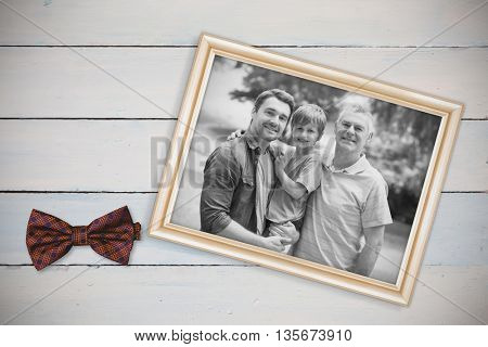 Grandfather father and son with family in background at park against white background with vignette