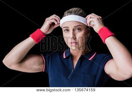 Female athlete adjusting her headband on black background