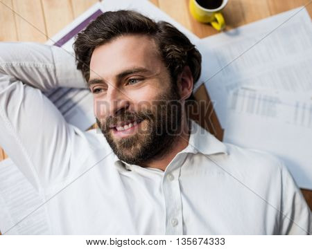 Man lying on the floor with his papers and coffee