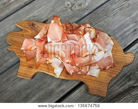 Tissue thin slices Tyrolean Speak, Smoked bacon (ham) on wooden cutting board