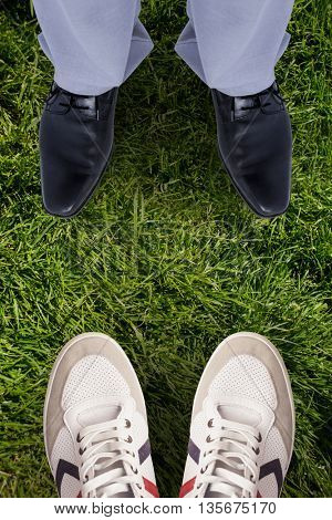 Low section of businessman against grass background