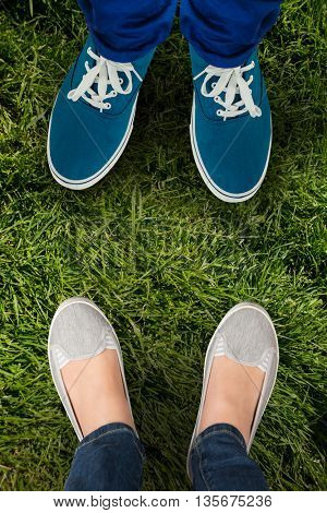 Man with canvas shoes on hardwood floor against grass background