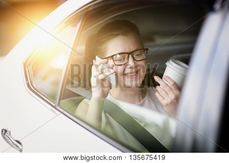 Woman In The Car Used Smartphone. Drinking A Beverage.