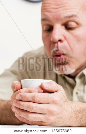 Close Up Of Man Blowing Into Cup