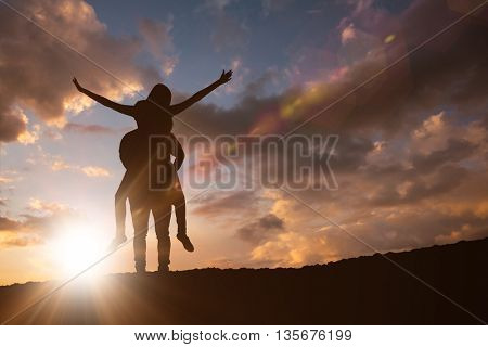 Happy casual man giving pretty girlfriend piggy back against clouds