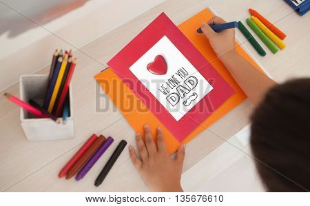 fathers day greeting against high angle of a girl drawing on orange paper at home